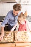 Fader och dotter som förbereder kakor för att baka i köket Arkivbild