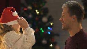 Fader och dotter som försöker på den Santa Clauses hatten och att ha roligt hemmastatt festligt lynne stock video