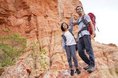 Fader och dotter som fotvandrar klättring i berg royaltyfri foto