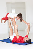 Fader och dotter som gör yogaelevatorn royaltyfri foto