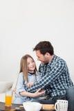 Fader och dotter som ger en kram i frukosten Arkivbild
