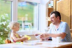 Fader och dotter som har frukosten Arkivbild