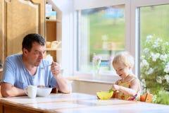 Fader och dotter som har frukosten Arkivbilder