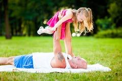 Fader och dotter som har gyckel i en park royaltyfria foton