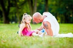 Fader och dotter som har gyckel i en park arkivfoton