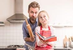 Fader och dotter som har gyckel i köket - baka Royaltyfri Foto