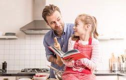 Fader och dotter som har gyckel i köket - baka Royaltyfria Foton