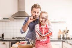 Fader och dotter som har gyckel i köket - baka Fotografering för Bildbyråer