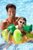 Fader och dotter som har gyckel i simbassäng Royaltyfri Bild