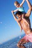 Fader och dotter som har gyckel på strand Arkivbilder