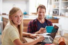 Fader och dotter som hemma använder bärbar datordatoren Arkivfoto
