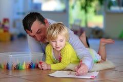 Fader och dotter som hemma tycker om familjtid Arkivbilder