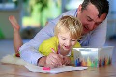 Fader och dotter som hemma tycker om familjtid royaltyfria bilder