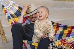 Fader och dotter som kopplar av i en hängmatta Royaltyfri Foto