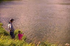 Fader och dotter som kopplar av, medan fiska royaltyfri fotografi