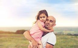 Fader och dotter som kramar på sommarsolnedgång arkivfoton