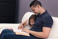 Fader och dotter som läser bibeln royaltyfri fotografi