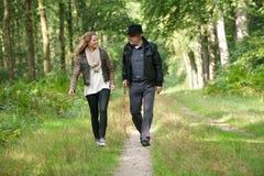 Fader och dotter som ler och går i natur royaltyfri foto