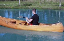 Fader och dotter som paddlar en kanot Royaltyfria Bilder