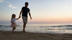 Fader och dotter som promenerar stranden arkivfilmer