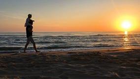 Fader och dotter som promenerar stranden på soluppgång lager videofilmer