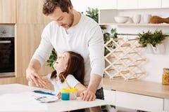 Fader och dotter som ser de, medan måla Royaltyfri Bild