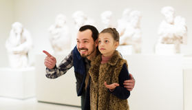 Fader och dotter som ser klassiska statyer Arkivfoto