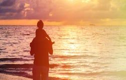 Fader och dotter som ser solnedgång på stranden Arkivfoto