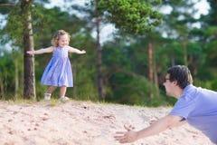 Fader och dotter som spelar i en skog Arkivbilder