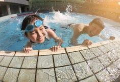 Fader och dotter som spelar i simbassäng arkivbilder