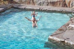 Fader och dotter som spelar i simbassäng arkivbild