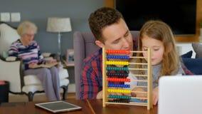 Fader och dotter som spelar med kulrammet i vardagsrum stock video