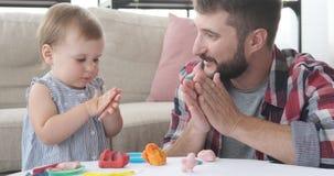Fader och dotter som spelar med plasticine lager videofilmer