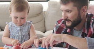 Fader och dotter som spelar med plasticine arkivfilmer