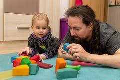 Fader och dotter som spelar med tegelstenar Arkivfoton