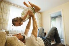 Fader och dotter som spelar på soffan i flygplanet bolts muttrar f?r sammans?ttningsbegreppsfamilj royaltyfria foton
