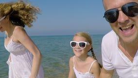 Fader och dotter som spelar på stranden stock video
