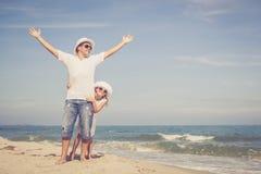 Fader och dotter som spelar på stranden på dagtiden arkivfoto