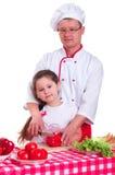 Fader och dotter som tillsammans lagar mat royaltyfri foto
