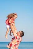Fader och dotter som tillsammans spelar på stranden Royaltyfria Foton