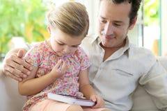 Fader och dotter som tillsammans spenderar tid hemma Arkivfoto