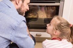 Fader och dotter som väntar på de hemlagade kakorna Royaltyfri Fotografi