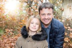 Fader och dotter tillsammans i parkeranedgångdagen med färgrik höst royaltyfri foto