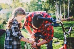 Fader- och dotterfixandeproblem med cykeln som är utomhus- i sommar arkivfoto