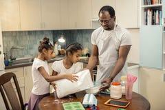 Fader- och dotterkänsla som gälls, i att laga mat pajen tillsammans royaltyfri foto