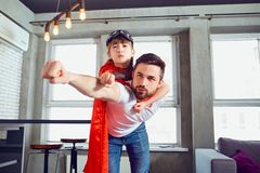 Fader- och dotterungen i toppen hjälte för dräkter spelar i rummet royaltyfri bild