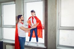 Fader- och dotterungen i toppen hjälte för dräkter spelar i rummet arkivbild