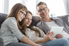 Fader och döttrar som hemma använder minnestavlaPC på soffan Royaltyfria Foton