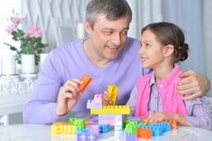 Fader och gullig liten dotter som sitter på tabellen och att spela royaltyfria foton