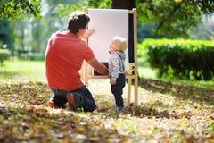 Fader och hans sonteckning utomhus fotografering för bildbyråer